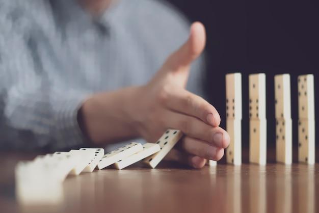Nahaufnahme männlicher stop-domino-fall mit der hand auf dem tisch auf dunklem hintergrund f