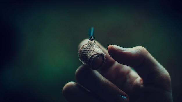 Nahaufnahme makroaufnahme eines glühwürmchens auf der hand eines mannes mit dunkelgrünem hintergrund