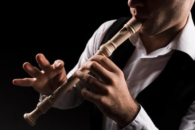 Nahaufnahme mann auf der bühne spielt die flöte