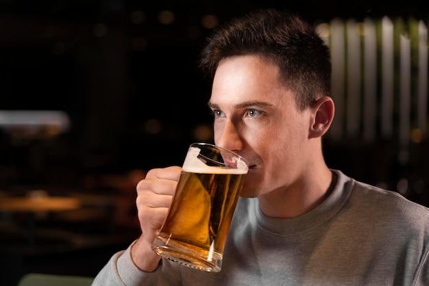 Nahaufnahme mann, der bier vom becher trinkt