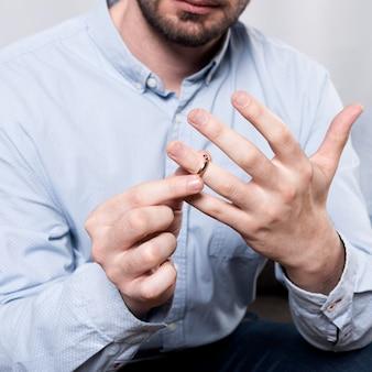 Nahaufnahme mann, der ehering vom finger nimmt