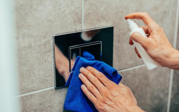 Nahaufnahme. mann, der ein antibakterielles spray auf einen wandschalter sprüht. foto mit einem exemplarplatz.