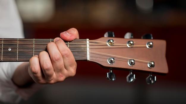 Nahaufnahme mann, der einen akkord auf gitarre hält