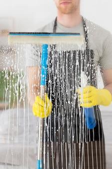 Nahaufnahme mann, der fenster reinigt