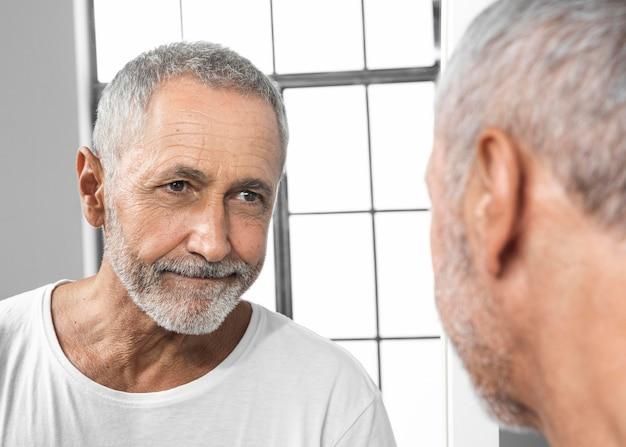 Nahaufnahme mann, der in den spiegel schaut