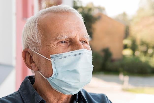 Nahaufnahme mann, der medizinische maske trägt