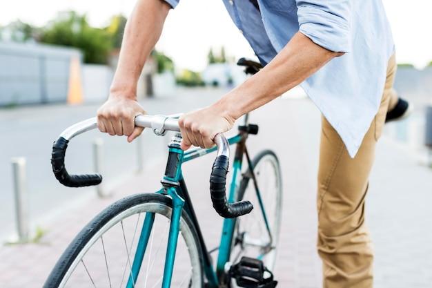 Nahaufnahme mann, der sein fahrrad klettert