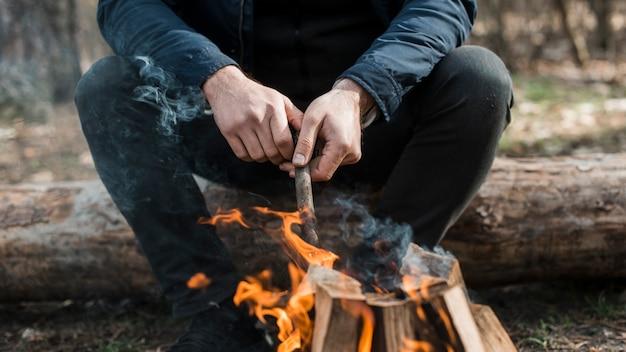 Nahaufnahme mann, der sich um lagerfeuer kümmert
