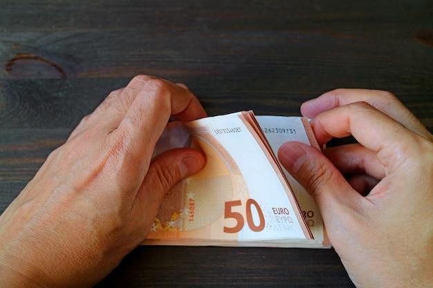 Nahaufnahme-mann-hände, die 50 eurobanknoten auf dunkler farbholztisch zählen