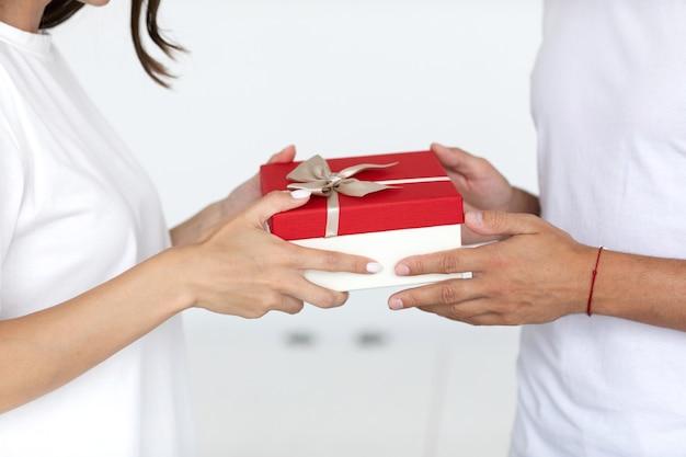 Nahaufnahme mann hände geben verpackte geschenkbox frau