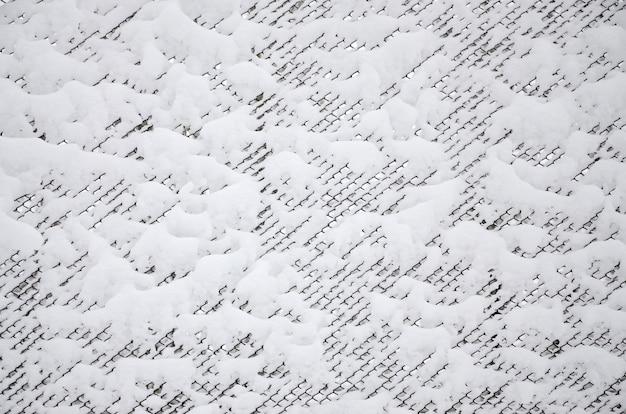 Nahaufnahme metallmasche bedeckt mit einer starken schneeschicht in den zellen