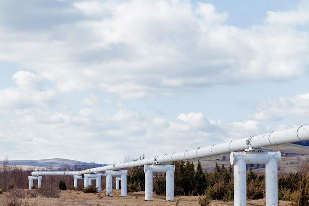 Nahaufnahme metallrohre im feld. rohre aus der pipeline. gasleitung zum pumpen von gas. wärmeleitung. großes silberfarbenes rohr für heißes wasser