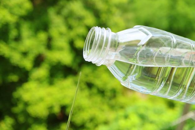 Nahaufnahme mineralwasser fließt aus einer plastikflasche mit verschwommenem grünem laub im hintergrund
