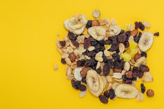 Nahaufnahme mischen nüsse und trockene früchte auf gelbem grund, das konzept der diät, richtige ernährung
