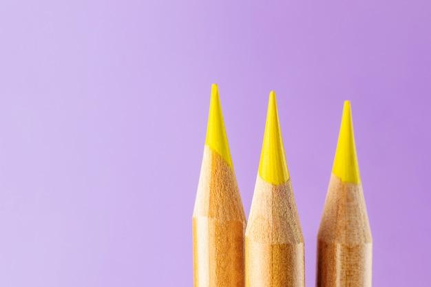 Nahaufnahme mit drei gelbe bleistiften auf einem lila hintergrund.