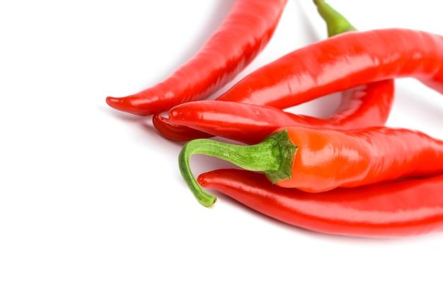 Nahaufnahme mit fünf pfeffern der roten paprikas auf weißem hintergrund
