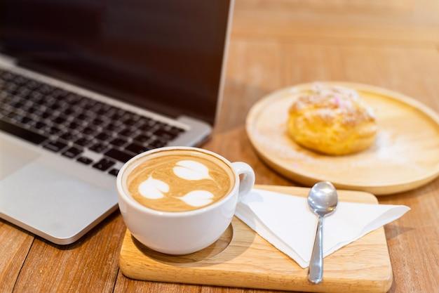 Nahaufnahme mit kaffeetasse, die mit laptop-computer und hausgemachten kränzchen mit choux-creme im kaffeehaus wie der hintergrund arbeitet