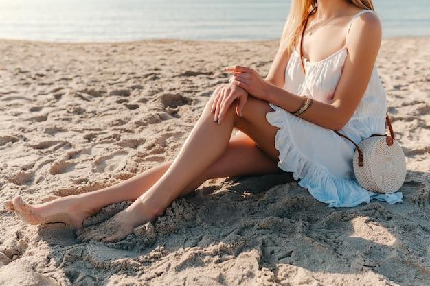 Nahaufnahme-modedetails der frau im weißen kleid mit strohbeuteltasche im sommerstil auf strandaccessoires