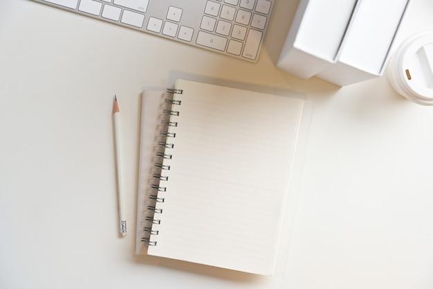 Nahaufnahme moderner arbeitsbereich mit weißem hintergrund und leeren seiten auf notizblöcken für ihre textanzeige