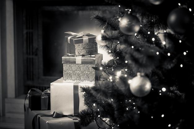 Nahaufnahme monochromes foto von weihnachtsgeschenken, die auf dem boden neben geschmücktem tannenbaum liegen