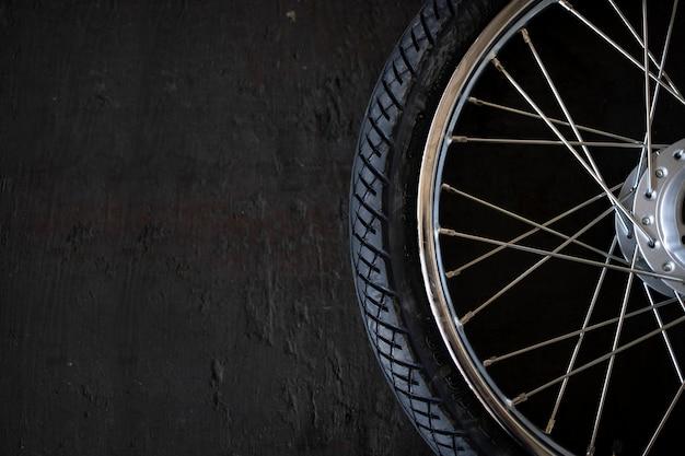 Nahaufnahme motorradreifen auf altem schwarzem holzhintergrund. draufsicht. flach liegen