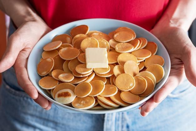 Nahaufnahme müsli pfannkuchen in der blauen schüssel mit stück butter in den händen der frauen
