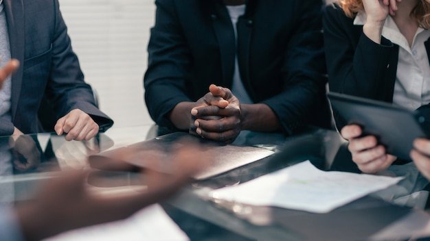Nahaufnahme. multiethnisches geschäftsteam, das bei einem bürotreffen neue ideen bespricht. mensch und technik