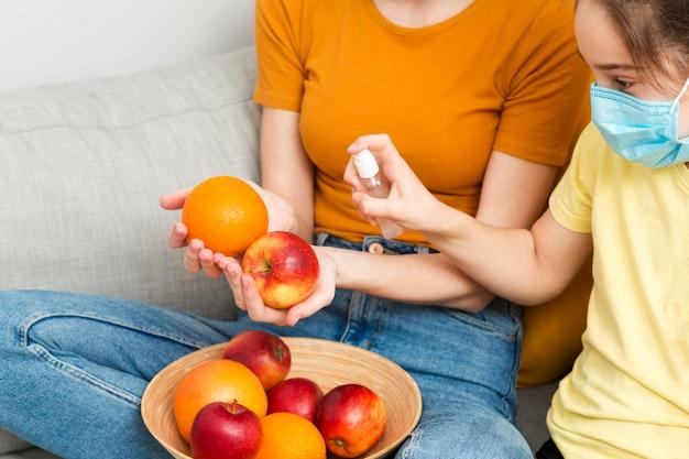 Nahaufnahme mutter desinfiziert früchte für mädchen