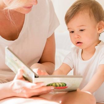 Nahaufnahme mutter, die baby im bett liest