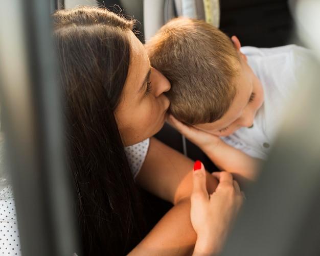 Nahaufnahme mutter küsst kind auf kopf