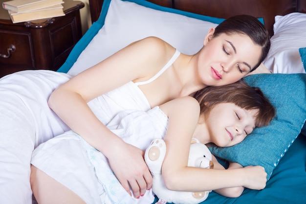 Nahaufnahme. mutter und kind umarmen und schlafen zusammen. studioaufnahme