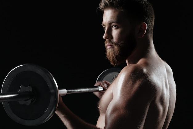 Nahaufnahme nackter muskulöser mann mit langhantel. isolierter dunkler hintergrund