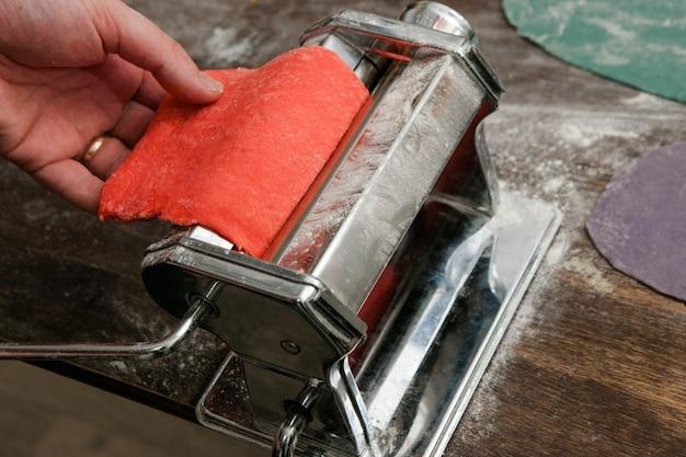 Nahaufnahme nudelmaschine prozess mit roten teignudeln auf holztisch