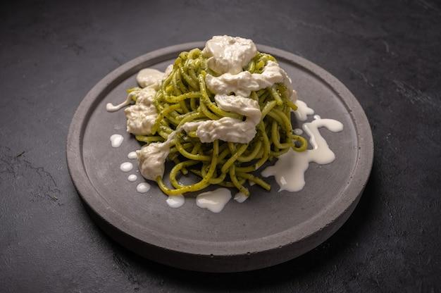 Nahaufnahme nudeln mit pesto, stracciatella-käse serviert auf grauer keramikplatte auf dunklem grafit-hintergrund, selektiver fokus
