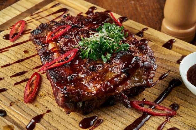 Nahaufnahme oben auf gerösteten barbecue-schweinerippchen in süß-saurer sauce mit salat auf einer holzoberfläche