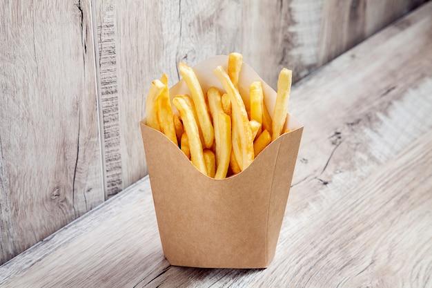 Nahaufnahme oben auf kartoffeln pommes frites in kartonverpackungsbox lokalisiert auf hölzernem hintergrund. fast-food-konzept modell. leerer kraft- oder bastelkarton mit pommes frites