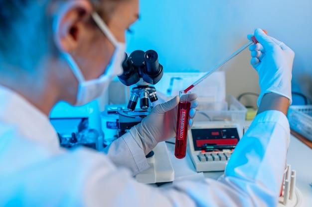 Nahaufnahme: optisches labormikroskop. diagnostisches reagenzglas in frauenhand mit weißem handschuh. analyse der klinischen blutprobe. wissenschaftliche forschung zum coronavirus