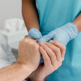 Nahaufnahme patienten und arzt händchen haltend