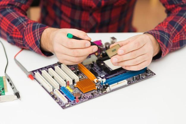 Nahaufnahme person, die ein motherboard repariert