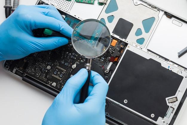 Nahaufnahme person, die einen laptop repariert