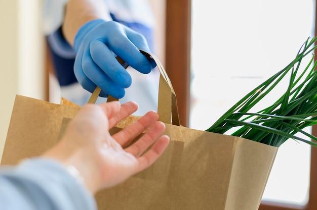 Nahaufnahme person, die online gekaufte lebensmittel erhält