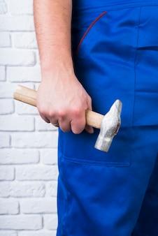 Nahaufnahme person im overall mit einem hammer