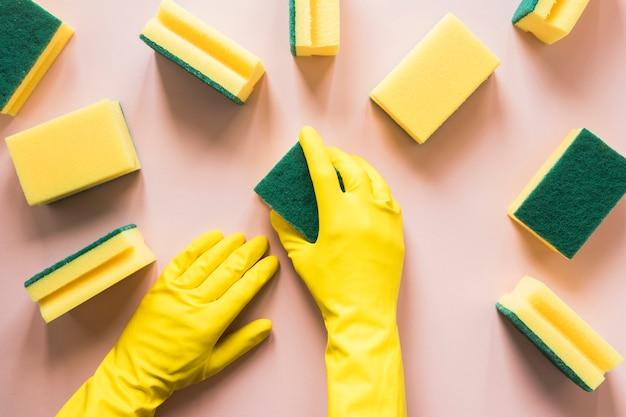Nahaufnahme [person mit gelben handschuhen und schwämmen