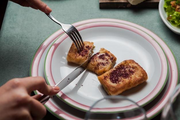 Nahaufnahme pfannkuchen mit fleisch hausgemacht in weißen teller auf einem servierten tisch mit einer anderen mahlzeit, messer, gabel horizontal