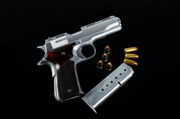 Nahaufnahme pistole mit goldenen scharfen kugeln auf einer schwarzen oberfläche