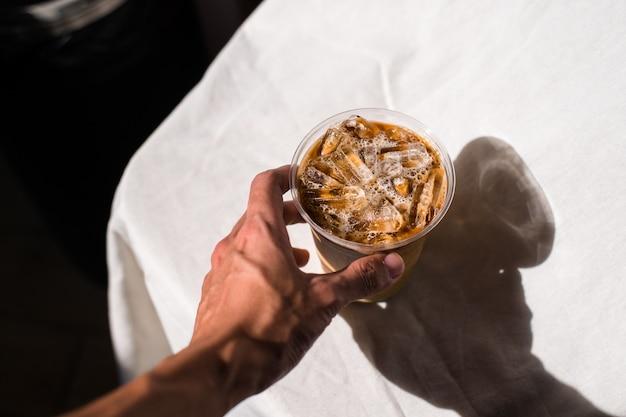 Nahaufnahme plastikbecher eiskaffee mit milch auf dem tisch