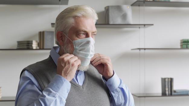 Nahaufnahme porträt älterer mann setzt eine medizinische maske auf sein gesicht, um sich vor coronavirus-pandemie zu schützen