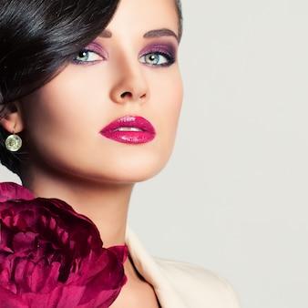 Nahaufnahme-porträt des schönheits-mode-modells mit make-up- und pfingstrosen-blume. niedliches gesicht