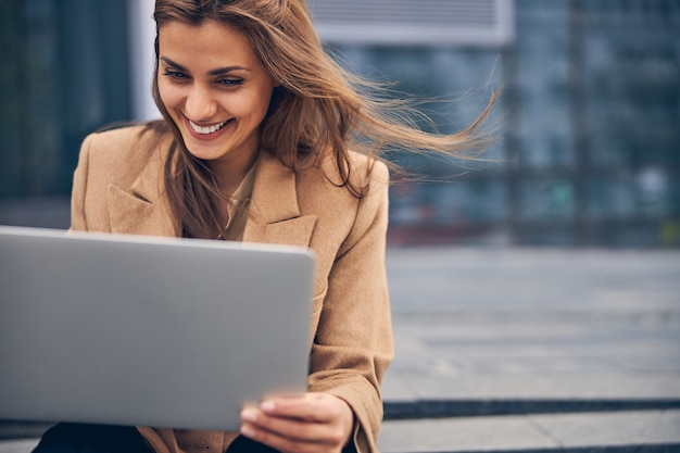 Nahaufnahme porträt einer attraktiven, fröhlichen, stilvollen kaukasischen freiberuflerin, die auf ihren computerbildschirm starrt