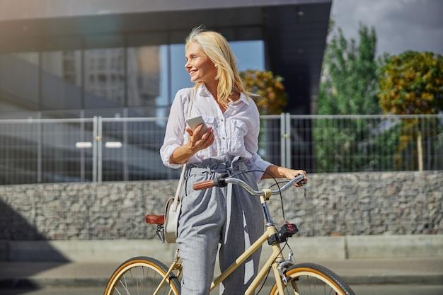 Nahaufnahme porträt einer attraktiven lächelnden frau in weißer bluse und grauer hose, die wegschaut, während sie mit ihrem fahrrad in der stadtstraße steht